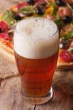 Крупный план холодного пива на предпосылке пиццы, вертикальной Стоковое Фото