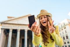 Крупный план цифровой фотокамера и женщины принимая selfie на пантеон Стоковые Фото