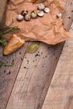 Крупный план части свежего багета, высушенной вверх по заливу выходит, яичка триперсток, раковины яичек на светлой деревянной пре Стоковая Фотография RF