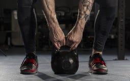 Крупный план человека фитнеса делая тренировку веса путем поднимать heav Стоковая Фотография
