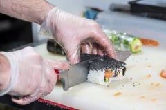 Крупный план шеф-повара подготавливая суши в кухне, отмелый DOF Стоковые Изображения RF