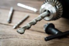 крупный план электрической дрели на деревянной предпосылке Стоковые Изображения RF