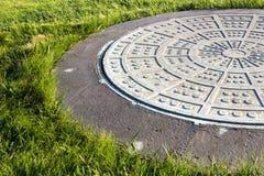 Крупный план люка -лаза и зеленой травы Стоковое Фото