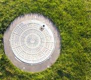 Крупный план люка -лаза и зеленой травы Стоковые Изображения