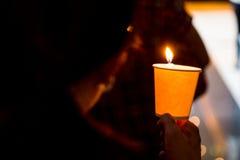 Крупный план людей держа дежурство свечи в темной ища надежде Стоковые Изображения RF