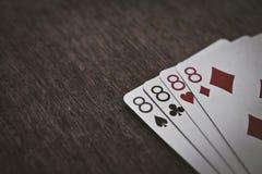 Крупный план eights играя карточек 4 на деревянном столе Стоковое Фото