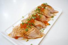 Крупный план salmon суш на белой плите с salmon косулями и прерванным луком весны Стоковая Фотография RF