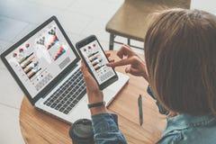 Крупный план smartphone с диаграммами, диаграммами и диаграммами на экране в руках усаживания молодой женщины стоковые фото
