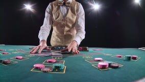 Крупье казино профессиональный шаркает карточки покера и фокус выполнять с карточками Черная предпосылка яркий свет видеоматериал