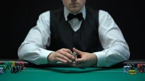 Крупье профессионально шаркая карточки покера перед камерой, играя в азартные игры сток-видео