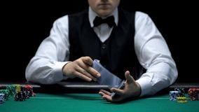 Крупье профессионально шаркая карточки покера перед камерой, играя в азартные игры стоковое изображение