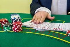 Крупье с обломоками и карточкой игры стоковое фото rf