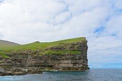Крутая скала около деревни Gjogv на острове Eysturoy, Стоковое Изображение