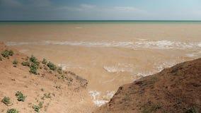 Крутое снижение к морю Море бурно и имеет цвет глины сток-видео