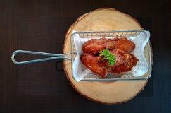 Крыла жареной курицы в металле жаря корзину металла служили на деревянной прерывая доске стоковые фото