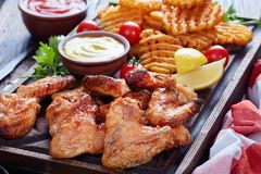 Крыла жареной курицы, кудрявые фраи картошки Стоковое фото RF