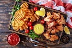 Крыла жареной курицы, кудрявые фраи картошки Стоковые Изображения