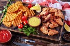 Крыла жареной курицы, кудрявые фраи картошки Стоковая Фотография