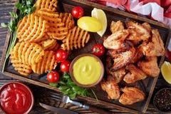 Крыла жареной курицы, кудрявые фраи картошки Стоковое Фото