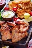 Крыла жареной курицы, кудрявые фраи картошки Стоковые Фото