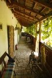 Крылечко деревенского дома родины с закручивая колесом и стендом стоковые фотографии rf