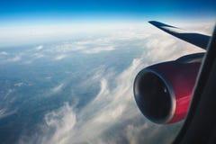 Крыло воздушных судн с розовым двигателем против неба пернатые облака от иллюминатора окна настроение каникул Стоковая Фотография RF