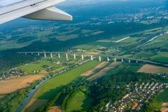 Крыло, деревня и мост над взглядом сверху реки от самолета стоковые изображения