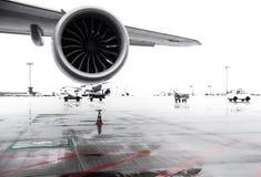 Крыло и двигатель двигателя авиалайнера на рисберме авиапорта на дождливый день Стоковая Фотография