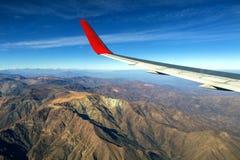 Крыло летания самолета над облаками утра и андийской горной цепью стоковое фото
