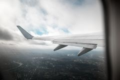 Крыло самолета в ненастной погоде Фото было принято от окна самолета Стоковое Изображение RF