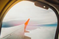 Крыло самолета в полете от окна, неба захода солнца Стоковое Фото