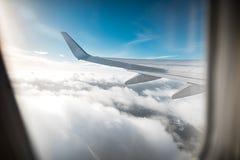 Крыло самолета над облаками, предпосылки голубого неба Фото было принято от окна самолета Стоковые Изображения RF