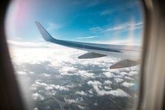 Крыло самолета над облаками, предпосылки голубого неба Фото было принято от окна самолета Стоковые Изображения