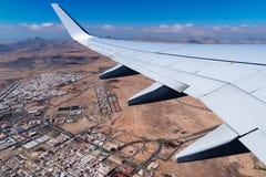 Крыло самолета принимая авиапорт Фуэртевентуры, над городом Стоковые Фотографии RF
