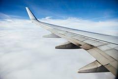 Крыло самолета против предпосылки облаков стоковое фото