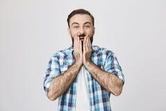 Крытая съемка европейского мужчины с бородой и усика, держащ обе руки на стороне, выражающ сюрприз и приятный стоковые изображения