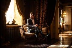 Крытая съемка зажиточного умного серьезного бизнесмена сидит на удобной софе в богатой комнате с роскошной мебелью стоковые изображения