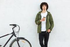 Крытая съемка красивого парня с вьющиеся волосы, одетая в модной куртке, черные брюки, напиток пить горячий, стоит близко bicyc стоковые фотографии rf