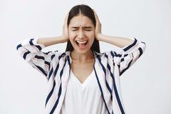 Крытая съемка поданной вверх расстроенной европейской женщины в striped блузке, выкрикивающ от депрессии, покрывая уши с ладонями стоковые фото