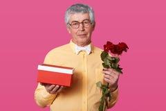 Крытая съемка пожилого джентльмена с серьезными владениями подарочно стоковое изображение