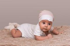 Крытая съемка прелестного женского малыша лежит на кровати на животе, смотрит с внимательным выражением в расстояние, замечает чт стоковое фото