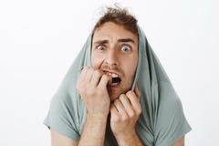Крытая съемка смешного вспугнутого кавказского парня с щетинкой, вытягивая футболку на голове и вытаращить с хлопнутыми глазами д стоковые фотографии rf