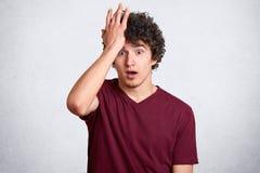 Крытая съемка студии потревоженного курчавого с волосами молодого человека касаясь его лбу с рукой, покрывающ ее, раскрывая глаза стоковые фото