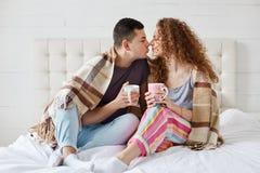 Крытая съемка счастливые женского и мужской имеет романтичные отношения, кофе напитка или чай, покрытые с шотландкой в спальне Ро стоковые фотографии rf