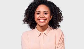 Крытый портрет счастливой Афро-американской молодой женщины, одетый в случайной бежевой рубашке, усмехается приятно на камере стоковое изображение