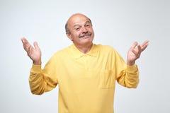 Крытый портрет confused старшего человека в желтом показе футболки я не имею никакой жест идеи стоковое фото rf