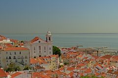 Крыть черепицей черепицей крыши традиционных домов, церков Graca и Рекы Tagus в городе Лиссабона, Португалии стоковые изображения