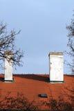 Крыша красной плитки с печной трубой на предпосылке голубого неба Стоковое фото RF
