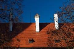 Крыша красной плитки с печной трубой на предпосылке голубого неба Стоковые Изображения RF