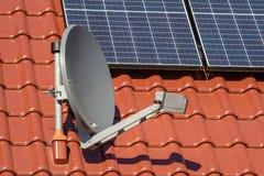 Крыша нового построенного дома с панелями солнечных батарей и спутниковой антенна-тарелкой стоковая фотография rf